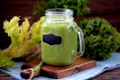 在金属螺盖玻璃瓶的健康圆滑的人从菠菜、黄瓜、芹菜、苹果、荷兰芹与橄榄油,喜马拉雅玫瑰色盐和矿物wate 库存图片