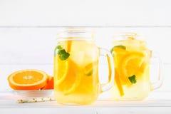 在金属螺盖玻璃瓶的橙色戒毒所水在一张白色木桌上 健康食物,饮料 图库摄影