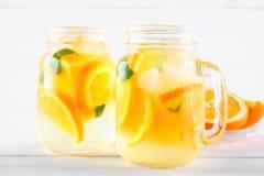 在金属螺盖玻璃瓶的橙色戒毒所水在一张白色木桌上 健康食物,饮料 库存照片