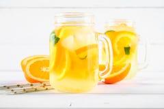 在金属螺盖玻璃瓶的橙色戒毒所水在一张白色木桌上 健康食物,饮料 免版税库存照片