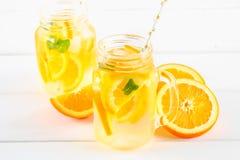 在金属螺盖玻璃瓶的橙色戒毒所水在一张白色木桌上 健康食物,饮料 免版税库存图片