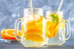 在金属螺盖玻璃瓶的橙色戒毒所水在灰色具体背景 健康食物,饮料 库存图片