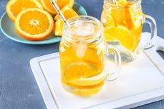 在金属螺盖玻璃瓶的橙色戒毒所水在灰色具体背景 健康食物,饮料 免版税库存照片