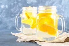 在金属螺盖玻璃瓶的橙色戒毒所水在灰色具体背景 健康食物,饮料 图库摄影