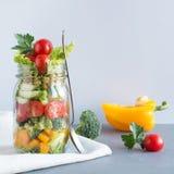在金属螺盖玻璃瓶的菜健康自创五颜六色的沙拉用蕃茄,莴苣,在蓝色的黄色papper 复制空间 工作的午餐 E 图库摄影