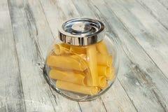在金属螺盖玻璃瓶的Canelones面团在明亮的土气木t提出了 图库摄影