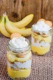 在金属螺盖玻璃瓶分层堆积的香蕉奶油色冷甜点 免版税库存图片
