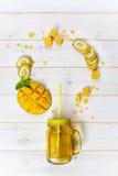 在金属螺盖玻璃瓶的芒果和香蕉圆滑的人有秸杆的 免版税库存图片