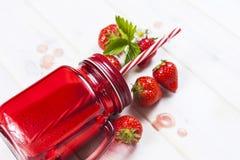 在金属螺盖玻璃瓶的草莓圆滑的人有秸杆的 库存图片