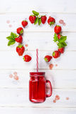 在金属螺盖玻璃瓶的草莓圆滑的人有秸杆的 免版税库存照片