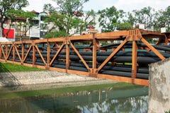 在金属路轨横穿河堆积的黑电导线在城市 免版税库存图片