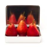 在金属配件箱的三个红色梨 免版税图库摄影