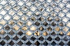 在金属链节篱芭的厚实的结冰的冰 免版税库存图片