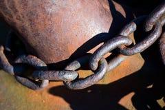 在金属系船柱附近的老生锈的锚链 免版税图库摄影