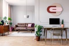 在金椅子旁边的有台式计算机的植物和书桌在与沙发的白色平的内部 免版税库存照片
