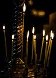 在金烛台的灼烧的蜡烛在黑色隔绝的教会里 图库摄影