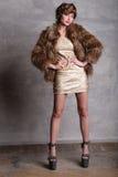 在金礼服和皮大衣的女孩模型在充分的高度 库存照片