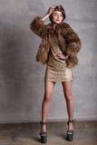 在金礼服和皮大衣的女孩模型在充分的高度 免版税库存照片