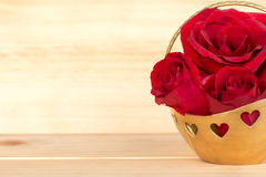 在金篮子,情人节,婚礼之日,木backg的红色玫瑰 免版税库存图片