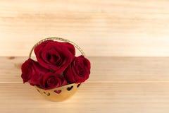 在金篮子,情人节,婚礼之日,木backg的红色玫瑰 库存图片