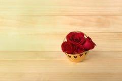 在金篮子,情人节,婚礼之日,木backg的红色玫瑰 库存照片