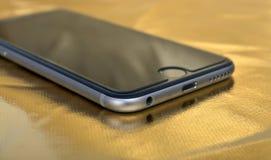 在金背景的智能手机特写镜头 免版税库存图片