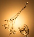 在金背景的白葡萄酒飞溅 图库摄影