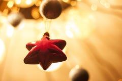 在金背景的红色星 发光的模糊的球 免版税图库摄影