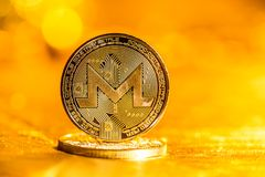 在金背景的Monero cryptocurrency 库存照片