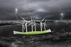 在金钱小船的风轮机在与风暴的黑暗 库存图片