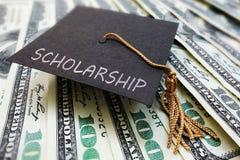 在金钱的奖学金盖帽 库存图片