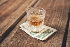 在金钱的威士忌酒玻璃 免版税库存图片