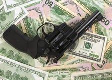 在金钱的黑左轮手枪一百元钞票 枪 图库摄影