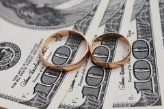 在金钱背景的婚戒  图库摄影