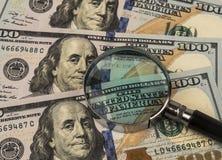 在金钱背景的放大镜  免版税库存图片