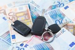 在金钱背景的汽车钥匙 免版税图库摄影