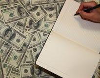在金钱背景的笔记本  库存图片