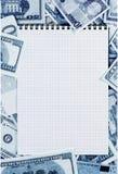 在金钱背景的被打开的螺旋笔记薄弄脏了蓝色 免版税图库摄影