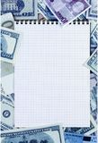 在金钱背景的被打开的螺旋笔记薄 被弄脏的蓝色 免版税库存图片