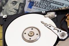 在金钱背景的被拆卸的硬盘 库存照片