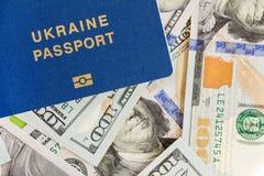 在金钱背景的Biometrical乌克兰护照 乌克兰公民说谎在美国的旅行文件一百美元钞票 v 免版税图库摄影