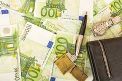在金钱100欧洲笔记背景的更轻的钱包时钟笔  免版税库存图片