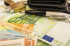 在金钱100欧洲笔记背景的更轻的钱包时钟笔  免版税库存照片