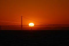 在金门大桥下的风船航行日落的 免版税库存照片