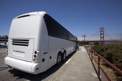 在金门大桥的白色游览宪章公共汽车 图库摄影