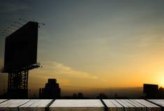 在金黄剧烈的城市天空的木展览架 库存图片