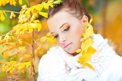 在金黄叶子中的小姐佩带的白色毛线衣 库存照片