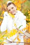 在金黄叶子中的小姐佩带的白色毛线衣 图库摄影