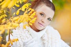 在金黄叶子中的小姐佩带的白色毛线衣 库存图片