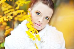 在金黄叶子中的小姐佩带的白色毛线衣 免版税库存照片